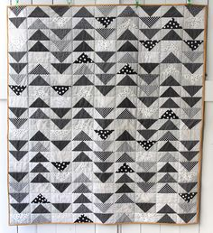 A lovely flying geese quilt created by Elaine Schurr McCardel of Beech Tree Lane Handmade! She had a vision to make a quilt with all black and white spotted fabrics, and we think she nailed it! She worked with various fabrics from her stash to create the flying geese using Bloc Loc Rulers. She quilted the quilt simply with Aurifil thread, so that that piecing remained the focus of the quilt. To see more, please visit: https://beechtreelanehandmade.com/2016/09/30/dotted-flying-geese-quilt/