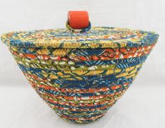 Handmade Multi Color Fabric Wrapped Clothesline Coiled Machine Stitched into a Basket with Flat Lid and Orange Wood Bead Knob by njbBasketofJewels on Etsy https://www.etsy.com/listing/222999877/handmade-multi-color-fabric-wrapped