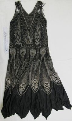 1920's beaded 'flapper' evening dress FromThe Kauri Museum ­ Matakohe Fine black crepe georgette sheath dress with heavy beading. Beading covers every inch of the crepe in clear glass, silver, black and gold, with floral and tear designs, with large peacock feather designs towards the skirt hem, where the material changes to taffeta with a handkerchief hem. Maker:Unknown Date Made: c.1920's