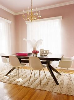 Such a feminine room.  I love the dark timber table against the pink walls, chandelier and white decor.