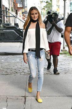 Olivia Palermo top blanco con escote off-the-shoulders, vaqueros claros desgastados, pañuelo negro y slippers amarillos.