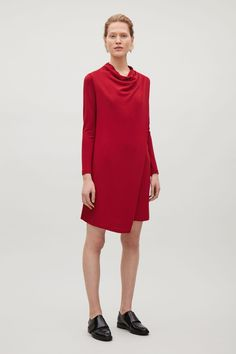 Made from a strecthy jersey material, this dress has draped front with a cowl neckline. An A-line fit, it has in-seam pockets, long sleeves and neat finishes.