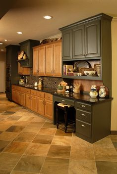 Existing oak cabinets used with some new painted cabinetry, counters, backsplash, and floors.