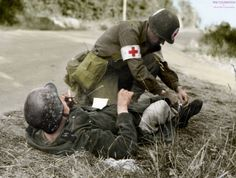 An American medic helping a wounded Waffen SS soldier, 1944.