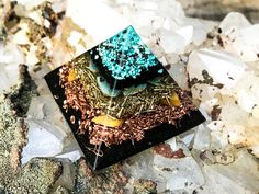 A shungite packed orgone pyramid to activate and align your energetic environment. A Quartz point floats at the tip to amplify the purifying energy of this orgone crystal pyramid. Layers of Turquoise, Shungite and Amazonite in a crystal grid align EMFs in a medium sized room grounding you and your space, while providing protection to your EMF. There are two layers of copper and brass and a base of my EMF Protection blend of iron oxide, iron, petalite, epidote, selenite and more Shungite…