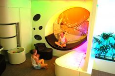 Sensory area organized with the round bins that roll out with more objects. Sitting area can change experience based on visual background.