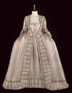 1770 The sack-back gown of cream silk woven with a deep mauve stripe and a small floral vine motif, with stomacher panel of the same silk, the gown decorated with ruching and flybraid; and with a matching petticoat, both lined in apple-green striped silk, French