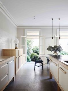 Sydney heritage house kitchen with flagstone floor and French limestone bench tops, burled maple veneer, Viabizzuno pendant lights and Domenico Mori wall tiles from Boffi.