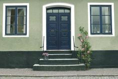 grönt putshus med blå dörr