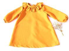 Vestido Colección Inés, elaborado en crep fino color mostaza con detalle de volante en cuello.