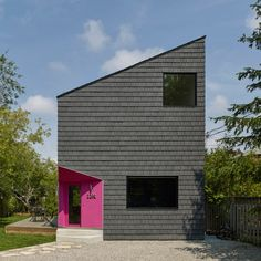 Toronto house features a hot pink entrance and is otherwise clad in black shingles
