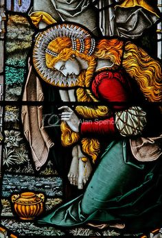 A stained glass window depicting Mary Magdalene kneeling at the foot of the Crucified Christ, Over Silton Church, North Yorkshire
