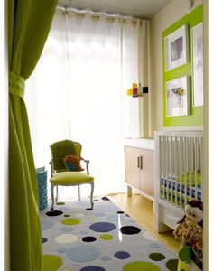 Fun, eclectic green & blue boy's nursery design with apple green walls paint color, modern white crib & changing table, green French chair, green curtains, turquoise blue lattice garden stool and blue green black dots rug.