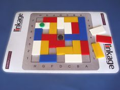 """This game is played on a 7x7 board with the center square blacked out. There are 24 pieces, 6 of 4 different colors. Each piece is a domino covering exactly two cells of the board. Both players choose pieces from a shared pool. There are two players in the game: the starting player is called """"More"""" and the other player is called """"Fewer"""". The goals of the game are opposite for both players. The """"Fewer"""" player wins a finished game if the n..."""