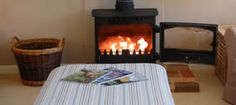 The cosy wood burning stove in the living room at Dormy House, a pet friendly holiday cottage in Suffolk with WiFi