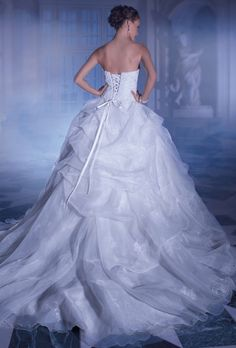 Brides: Demetrios - Sposabella. Strapless, organza gown with asymmetrical pleating on bodice. Sweetheart neckline and full skirt with bustles and pick-ups. Bodice and skirt are embellished with beaded Venice appliques. Back finished with lace-up and chapel train with bustles.
