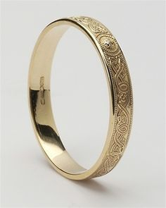 Wedding ring in 14k yellow gold delicately embossed with ancient Celtic symbols made by master artisans in Dublin, Ireland....