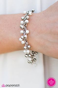 Dainty white pearls and silver beads delicately fall from the wrist in a refined…