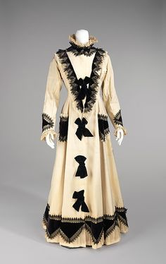 Ivory wool tea gown with black silk velvet and black lace decoration (front), American, 1875. Worn by Amelia Beard Hollenback (1844-1918), wife of the prominent financier and philanthropist John Welles Hollenback (1835-1927), in the months immediately after the Hollenback's first daughter was born, this early example illustrates Amelia Hollenback's keen awareness of fashion. Teagowns, which were worn as at-home attire when entertaining guests, made their first appearance in the late 1870s.