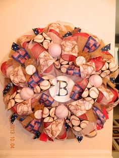 Deco Mesh Baseball Wreath   This deco mesh baseball wreath would look beautiful on any door. With Red, white and blue ribbon and mesh with a hint of burlap finishes this wreath. I was inspired by my son playing ball, I thought about the things that I would want to include when displaying a wreath on my front door. I hope you enjoy it as much as I do.  **Note: A small initial can be added to the baseball in the center to make it a custom wreath**
