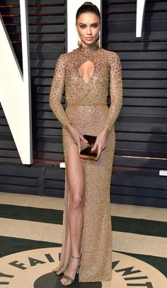 ADRIANA LIMA in a high-slit keyhole cutout champagne Labourjoisie gown, Lee Savage clutch and Chopard gems for the Vanity Fair after party.