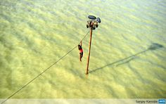 INDIA, Allahabad : An Indian youth dangles from a power line before diving into the floodwaters of an overflowing Ganges river in Allahabad on August 6, 2013. The monsoon, which covers the subcontinent from June to September and usually brings flooding, accounts for about 80 percent of India's annual rainfall. AFP PHOTO/ SANJAY KANOJIA
