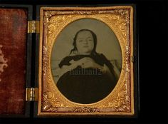 Ambrotype of a deceased little girl in a black dress peacefully posed for a final portrait
