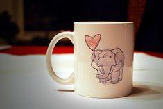 White ceramic mug featuring a cute watercolor illustration of an elephant holding a heart-shaped balloon.