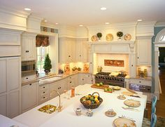 This dream kitchen was designed by Amy Norris, CKD.  Vintage beaded inset doors with Windsor drawer heads.  The kitchen features:      *Vent-a-Hood stainless steel liner      *Sub-Zero 642O refrigerator      *Venetian Gold Granite coutertops      *Enkeboll hand-carved corbells and mantel molding      *Top Knobs decorative hardware      *Hera undercabinet lighting