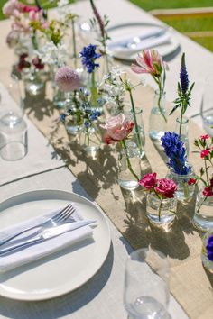 Wedding centrepiece created using single stems of vibrant pink, purple and blue spring flowers in glass bottles