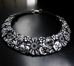 This is a distressed collar necklace created entirely from polymer clay. It has been sculpted, sanded, and painted by hand to render its frosted