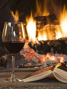 Glass of wine and book by fireplace