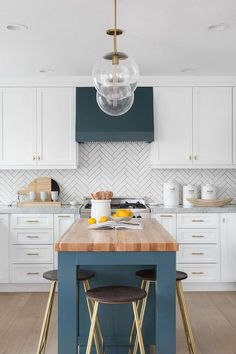Gorgeous blue and white kitchen features a blue hood fixed between white shaker cabinets to a white herringbone backsplash.