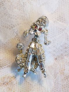 Vintage Pell fancy white rhinestone Poodle with red rhinestone eyes pin brooch. $18.00, via Etsy.