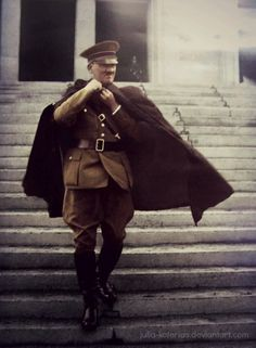 Adolf Hitler sporting a shall, descends the stairs of a German government building on a cool, Northern European day.
