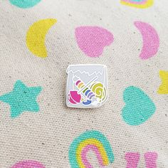 This cute little bag of sweets pin features 7 different hard enamel colours. This pin is tiny! It measures 1.4cm x 1.5cm and has a clutch back.