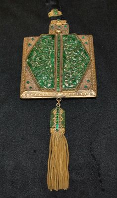 1920s carved faux jade dance purse fabricated in celluloid to appear like genuine jade on a filigree base. This is further enhanced with emerald color glass stones both on the purse as well as on the accented handle. Marked Trinity Plate on the interior rim, the back and interior contains the original silk, in good condition but is beginning to show some fraying. The change purse and original mirror is included as well. Measures 8.25 inches from top of to bottom of tassel.
