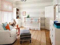 chambre de bébé claire avec une peinture à rayures grises et blanches, un tapis beige clair et des meubles blancs