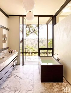 The airy master bathroom features pendant lights from Masters of Modernism   archdigest.com