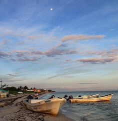 The first rays of sunrise strike fishing boats on the northern coast of the Yucatan peninsula as the fishermen get ready to go to work in the Gulf of Mexico and the full moon sets.  Stay tuned for some exciting information about our #PassportswithPurpose prize :) #latergram