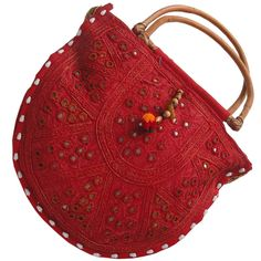 This bright red Rajasthani hand bag in round shape can easily attract any female. This pretty bag is enhanced with intricate lace work by our creative artisans. It is decorated with mirror work presents a good example of traditional craftsmanship of Rajasthan. The beauty of this hand bag is tassels stitched all over. The cane wood handle of this bag is making it trendy yet modern.
