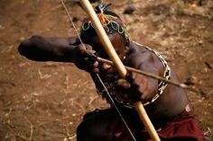 Hadzabe man with bow and arrow. The Hadzabe live about 15-hundred miles north of the San near Tanzania's Serengeti. They split from the founding population (the San) around 150,000 years ago. Today the Hadzabe are one of the last groups of hunter-gatherers on Earth.