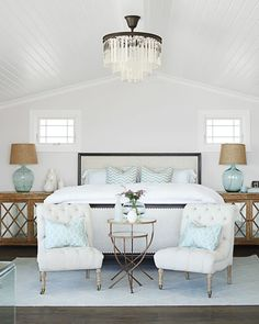 This home's designer, Becky Owens, made a cozy nook at the foot of the bed with two tufted chairs.