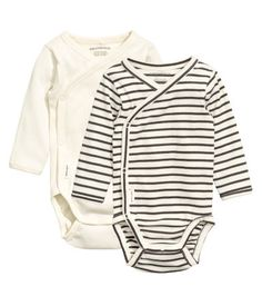 H&M CONSCIOUS. Wrap-style bodysuits in soft organic cotton jersey with long sleeves and snap fasteners at side and at gusset. One patterned and one in ribbed jersey.