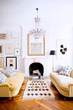 Why It Works: Double Sofas // yellow sofa, fireplace, crystal chandelier, gallery wall