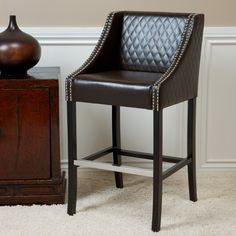 Perfect for a kitchen island, business, or at-home bar, this tufted leather bar stool is comfortable and stylish. The seat is smooth, with a tufted back and sides and fierce studding down the arms. This sleek bar stool is a force to be reckoned with.