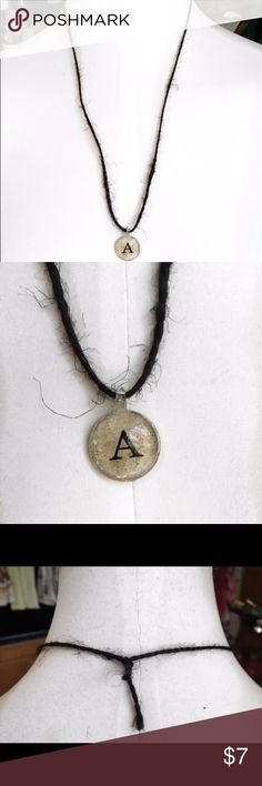 Handmade Black Twine Initial A Necklace Beautiful, handmade black twine necklace featuring a silver-coated beige pendant with the initial 'A' in the center. Approx. 12 inches long, including pendant. Only one available. Handmade Jewelry Necklaces