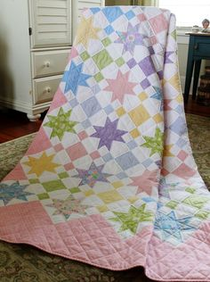 This would be easy to make up a pattern.  It's a simple star block and alternating with a variation nine patch block all set on point.  The border is formed by solid pink blocks and half blocks.  Love how light and spring like it is.