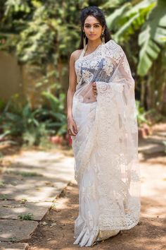 You would look like a fairy from fairyland in this gorgeous white lacy net saree! With a threadwork border and pearl detailing for the pallu. Have all eyes upon you as gracefully descend down the stairs. White on white is a dreamy pairing any day. Or mix things up a bit by choosing a blouse in a pastel color. #houseofblouse #saree #blouse #indianwear #india #fashion #bollywood #white #lace #net