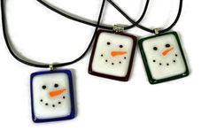 What a fun necklace to wear during the Christmas and winter season! So cute with that favorite sweater. They are great for gift giving as well and for all ages. We hand cut the glass and layered the white on pieces of Christmas red, Christmas green and royal blue. After the white glass was added to the red glass, the faces were hand painted with glass paint. The paint is actually crushed glass mixed with a medium, so when fired, it becomes permanent. Because they were hand painted, each one…